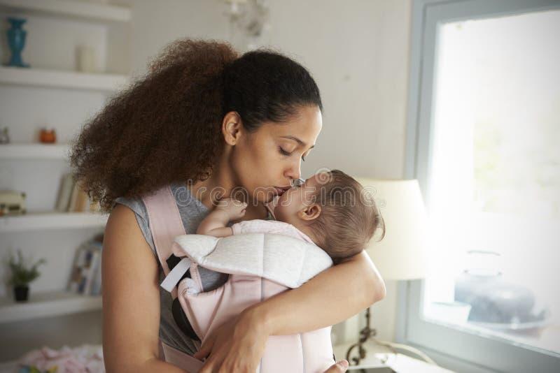 Fille de caresse de bébé de mère à la maison en Front Of Window photo libre de droits