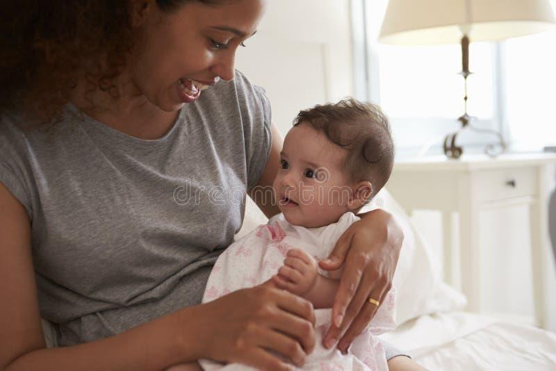 Fille de caresse de bébé de mère dans la chambre à coucher à la maison images libres de droits