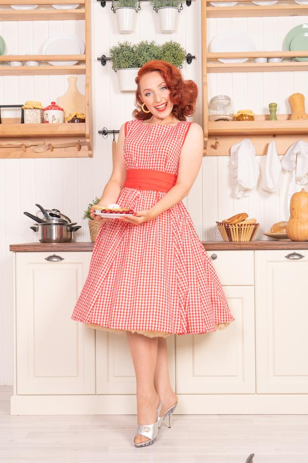 Fille de charme avec les cheveux rouges dans le rétro style posant dans une robe de cru dans la cuisine images libres de droits