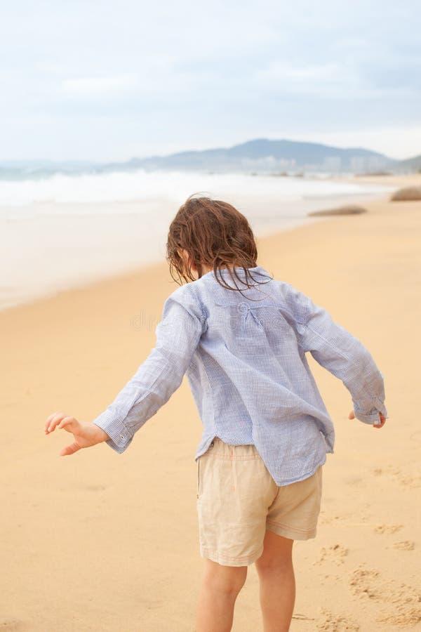 Fille de cinq ans jouant sur la plage sablonneuse de la mer image stock