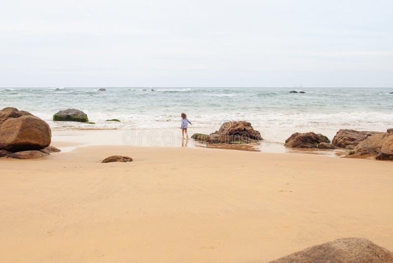 Fille de cinq ans jouant sur la plage sablonneuse de la mer photo stock