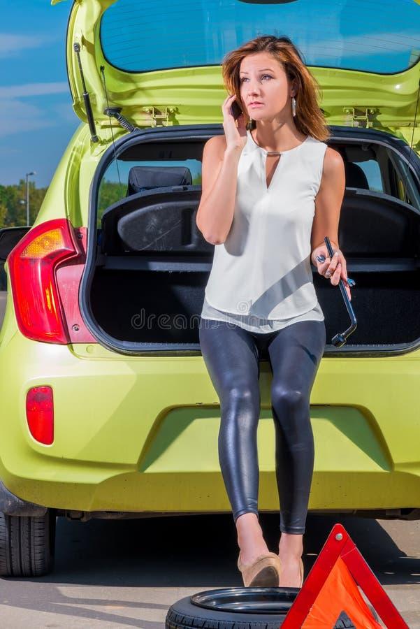 Fille de conducteur appelle le mécanicien se tenant près de la voiture photographie stock libre de droits