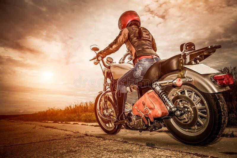 Fille de cycliste sur une moto photographie stock