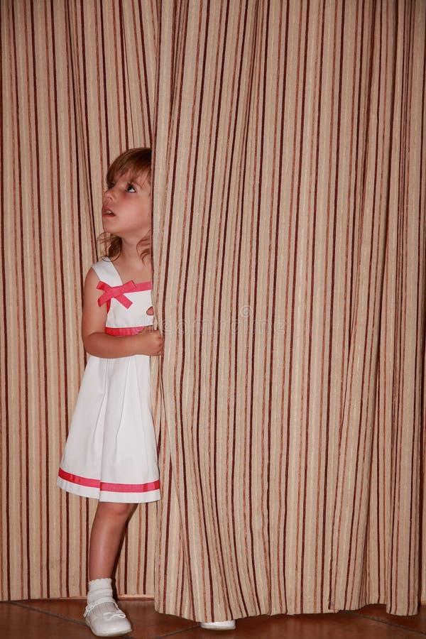 Fille de Dela derrière le rideau photos stock