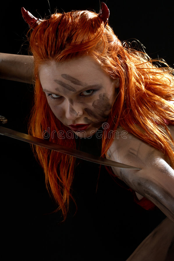 Fille de diable rouge avec un couteau   photo libre de droits