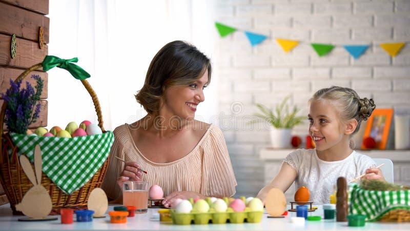 Fille de enseignement de femme pour peindre des oeufs pour des vacances de Pâques, leçon d'art, faite main photo stock