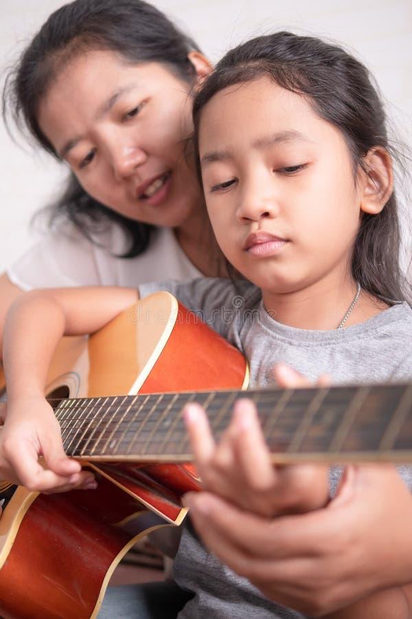 Fille de enseignement de mère jouer une guitare images stock