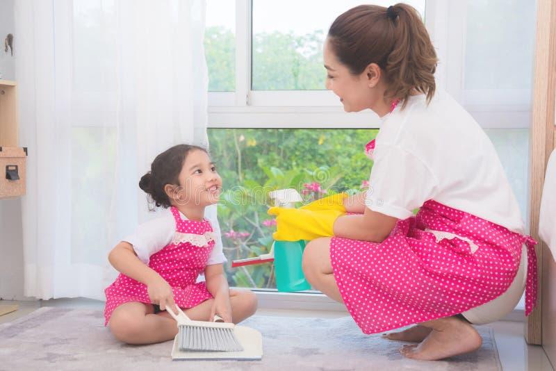 Fille de enseignement de mère nettoyant leur maison photos stock