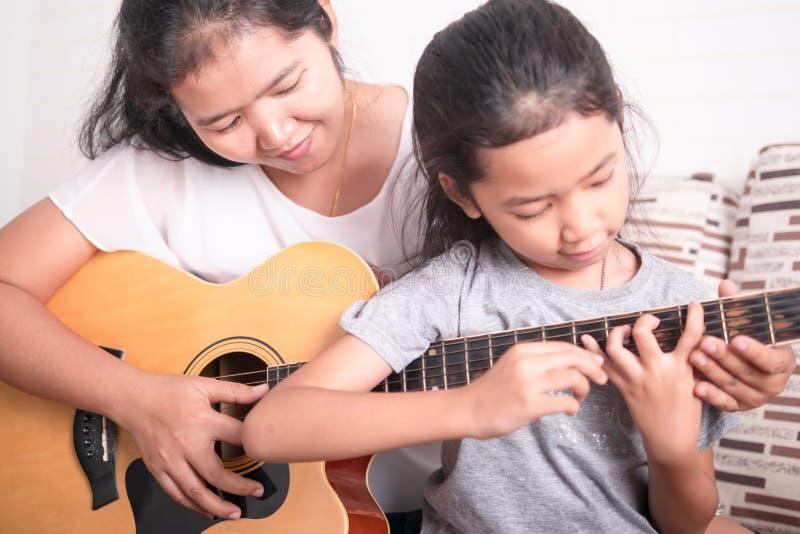 Fille de enseignement de m?re pour jouer la guitare photo libre de droits