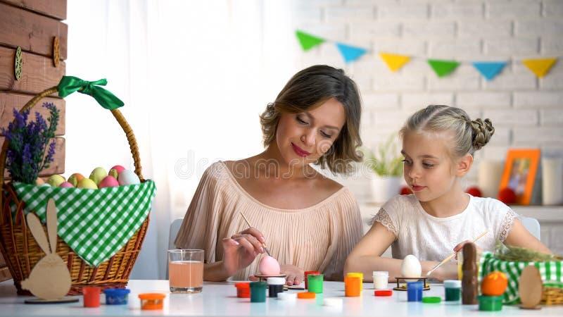 Fille de enseignement de maman comment colorer des oeufs de pâques, famille se préparant aux vacances photo libre de droits
