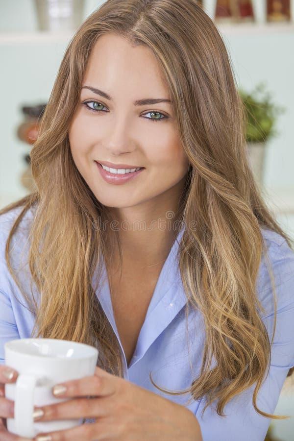 Fille de femme en thé ou café potable de cuisine photographie stock libre de droits