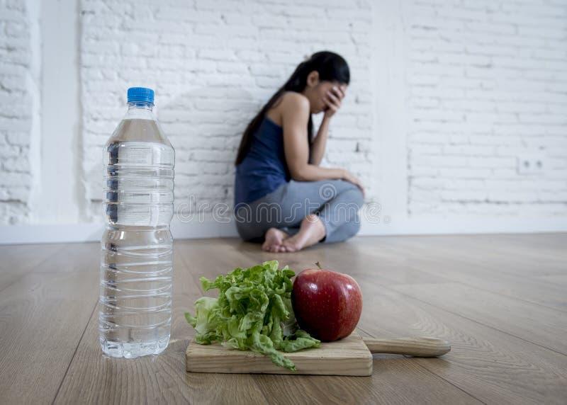 Fille de femme ou d'adolescent s'asseyant sur le seul à la maison trouble de la nutrition de souffrance inquiété au sol de nutrit photographie stock