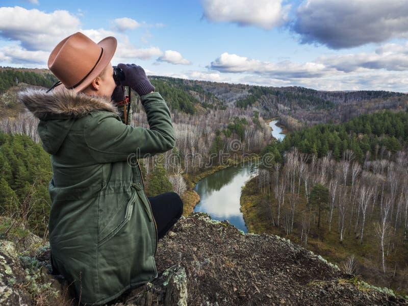 Fille de femmes appréciant le coucher du soleil sur des jumelles rivière et forêt images stock