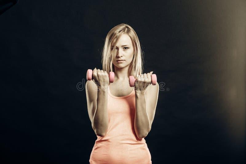 Fille de forme physique avec des haltères fléchissant des muscles dans le gymnase photo stock
