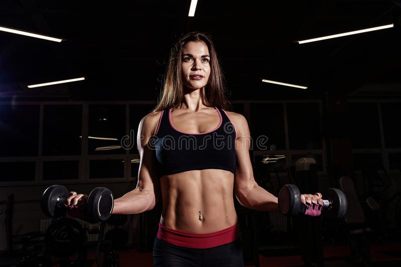 Fille de forme physique de bikini établissant avec des haltères Femme d'athlète dans les vêtements de sport faisant l'exercice da image libre de droits