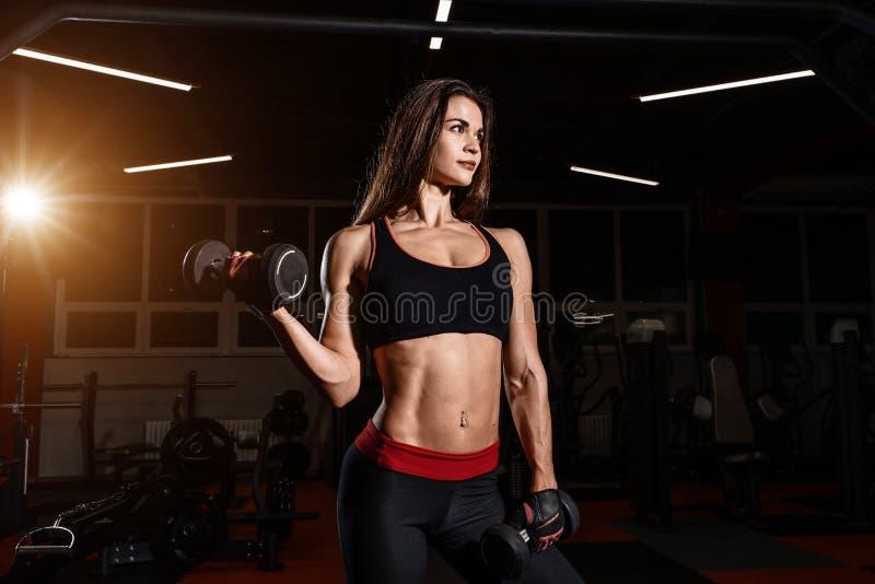 Fille de forme physique de bikini établissant avec des haltères Femme d'athlète dans les vêtements de sport faisant l'exercice da photos stock