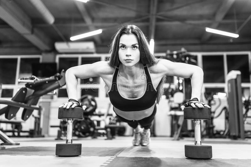 Fille de forme physique de bikini établissant avec des haltères Femme d'athlète dans les vêtements de sport faisant l'exercice da photo libre de droits