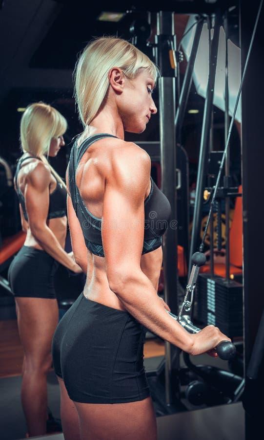 Fille de forme physique dans l'usage noir de sport avec le corps parfait image libre de droits