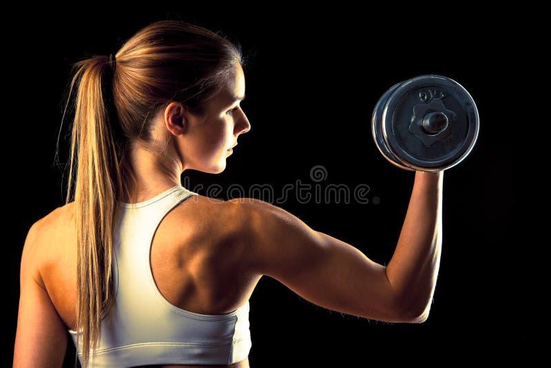 Fille de forme physique - jeune femme attirante établissant avec des haltères photographie stock libre de droits
