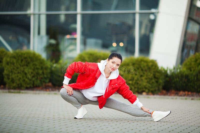 Fille de forme physique Jeune femme de sports s'?tirant dans la ville moderne Mode de vie sain dans la grande ville images libres de droits