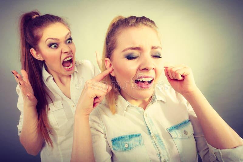 Fille de fureur criant à son ami, fermeture femelle ses oreilles images stock