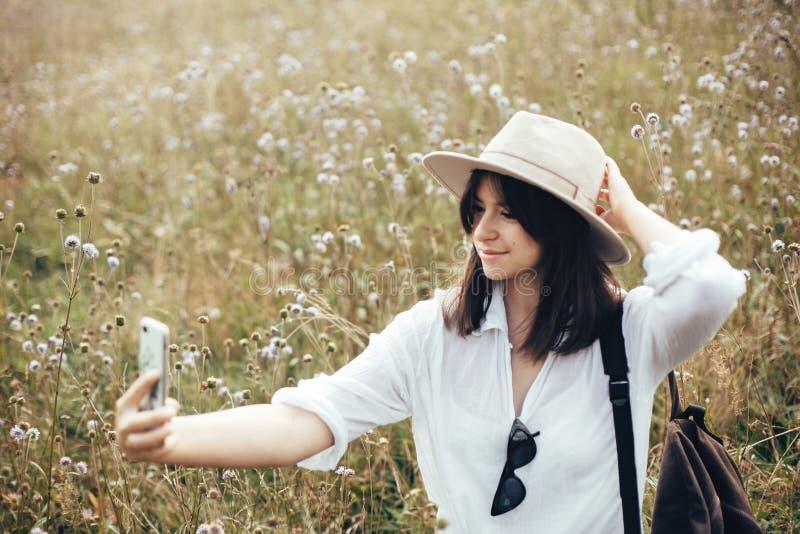 Fille de hippie avec le sac à dos prenant le selfie au téléphone tout en détendant dans le pré de wildflower, voyageant en montag image libre de droits