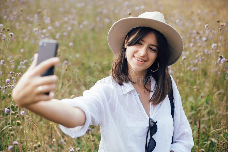 Fille de hippie avec le sac à dos prenant le selfie au téléphone tout en détendant dans le pré de wildflower, voyageant en montag photo stock