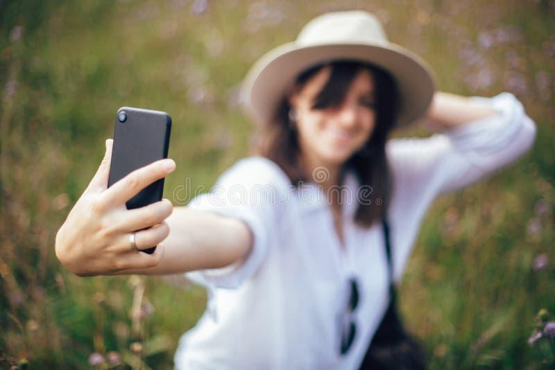 Fille de hippie avec le sac à dos prenant le selfie au téléphone tout en détendant dans le pré de wildflower, voyageant en montag image stock