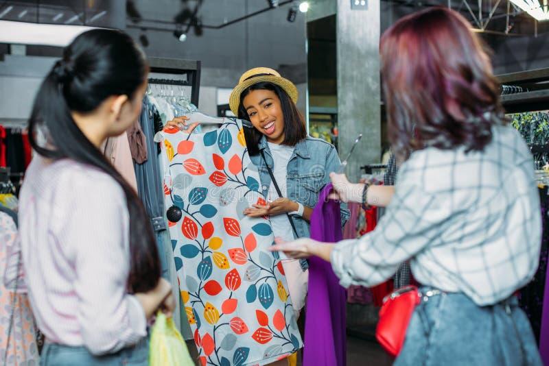 Fille de hippie d'afro-américain avec des amis choisissant des vêtements dans la boutique image libre de droits