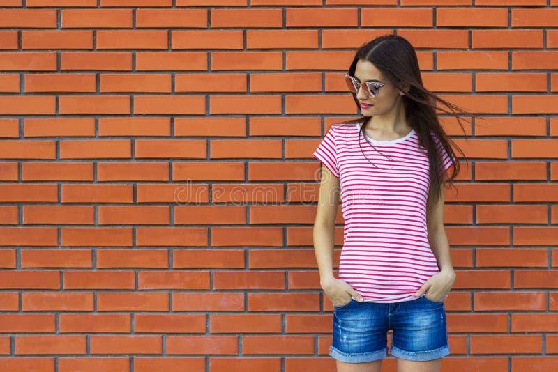 Fille de hippie portant le T-shirt, les lunettes de soleil rouges et blanches de mode et les caleçons rayés de jeans posant sur l image stock