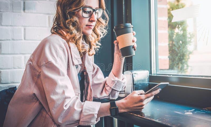 Fille de hippie s'asseyant en café à la table noire, café potable et à l'aide du smartphone Femme d'affaires travaillant en ligne photos stock