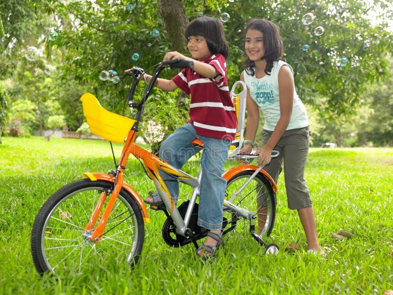 fille de jardin de cycle son équitation photo stock