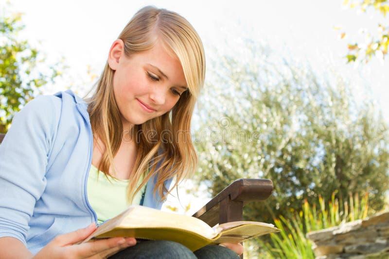 Fille de jeune adolescent en dehors de la lecture images libres de droits