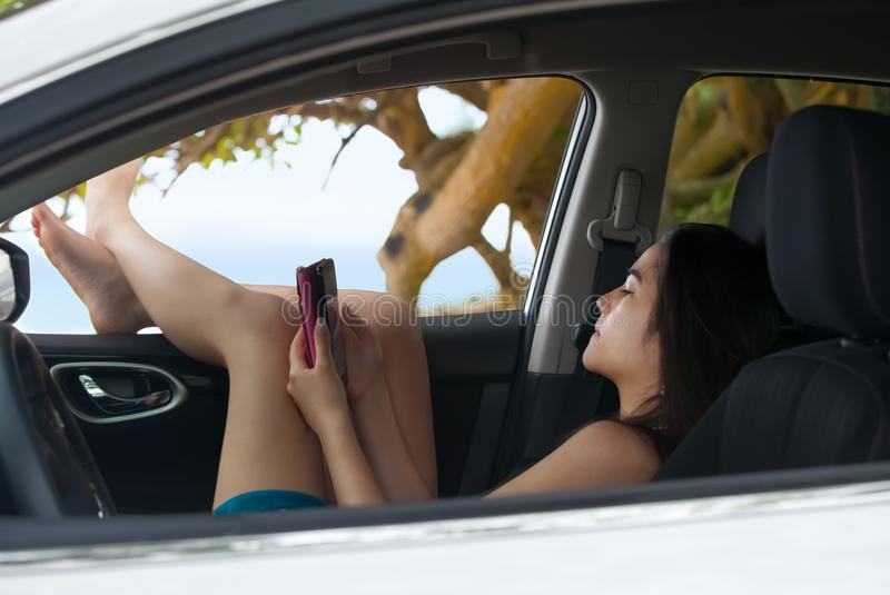 Fille de l'adolescence à l'aide du smartphone détendant avec la fenêtre de voiture de jambes  images libres de droits