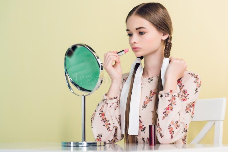 fille de l'adolescence élégante appliquant le rouge à lèvres avec le miroir photo stock