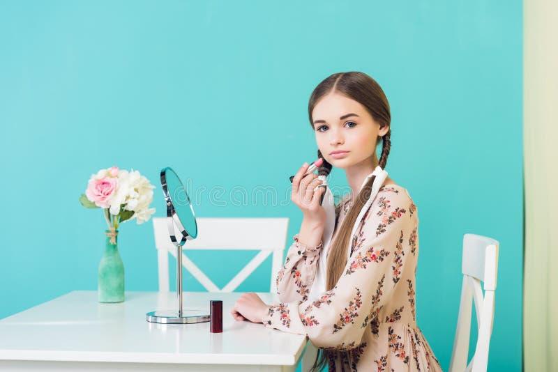 fille de l'adolescence élégante attirante appliquant le rouge à lèvres avec le miroir photos libres de droits