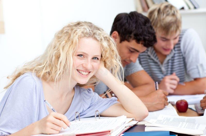 Fille de l'adolescence étudiant dans la bibliothèque avec ses amis images libres de droits