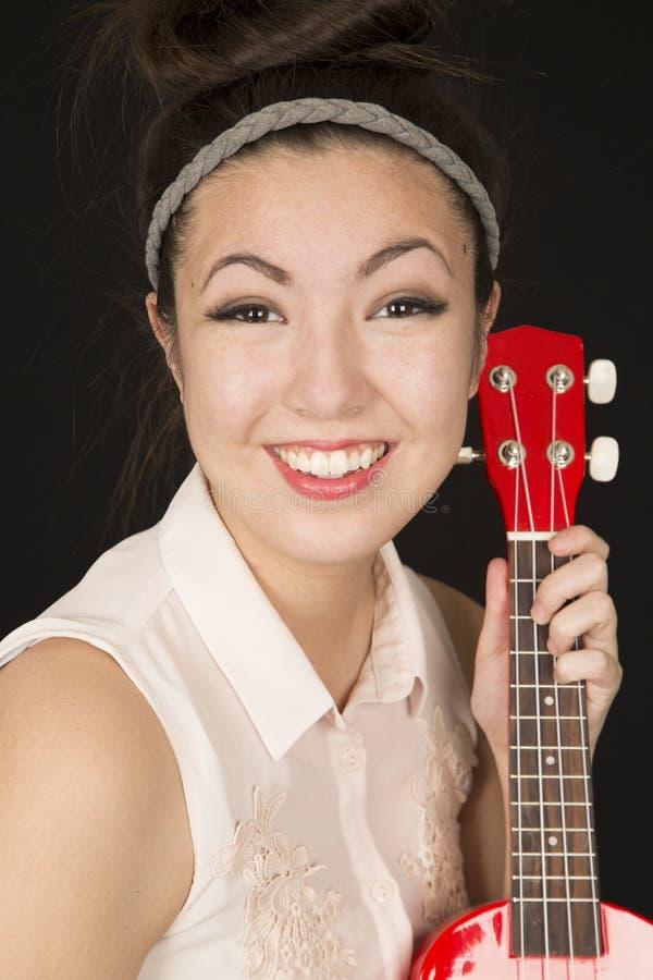 Fille de l'adolescence américaine asiatique mignonne tenant une ukulélé image libre de droits