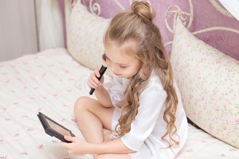 Fille de l'adolescence appliquant le maquillage se reposant sur un lit image stock