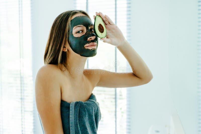 Fille de l'adolescence appliquant le masque facial d'argile noir avec l'avocat photo stock