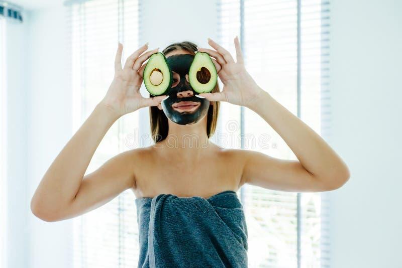 Fille de l'adolescence appliquant le masque facial d'argile noir avec l'avocat photographie stock