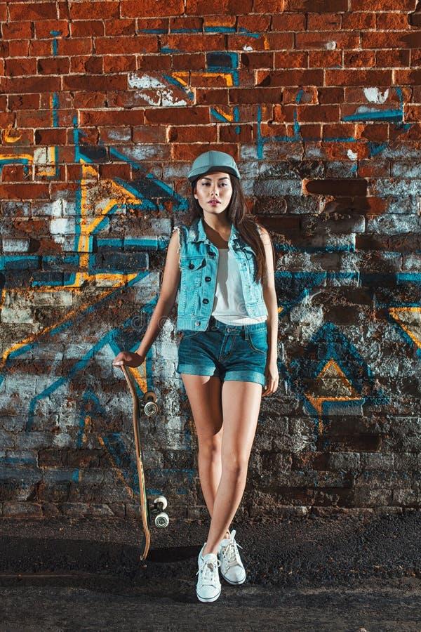 Fille de l'adolescence avec le panneau de patin, mode de vie urbain photographie stock