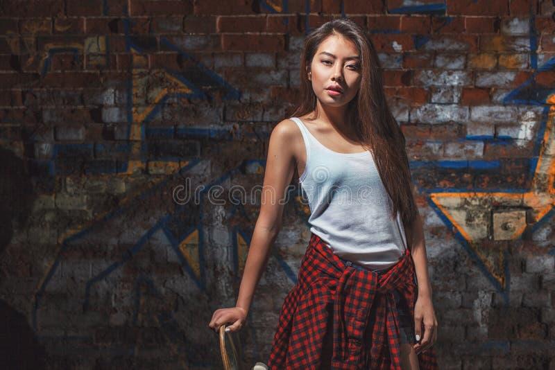 Fille de l'adolescence avec le panneau de patin, mode de vie urbain image libre de droits