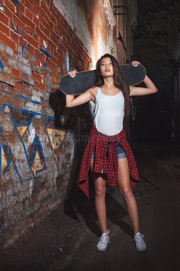 Fille de l'adolescence avec le panneau de patin, mode de vie urbain photos libres de droits
