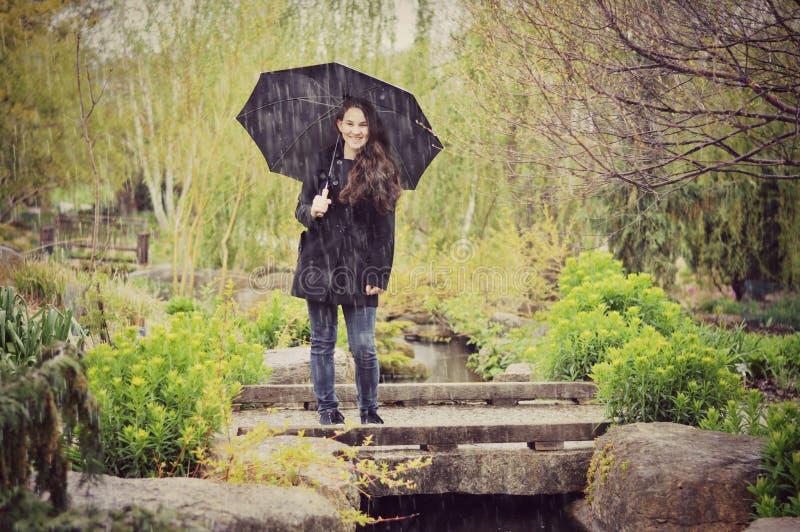 Fille de l'adolescence avec le parapluie sous la pluie image libre de droits
