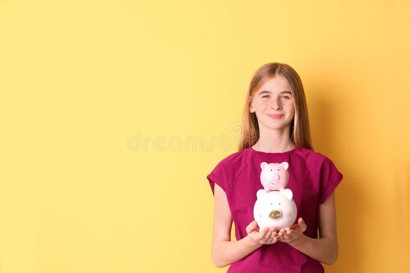 Fille de l'adolescence avec les tirelires sur le fond de couleur images stock
