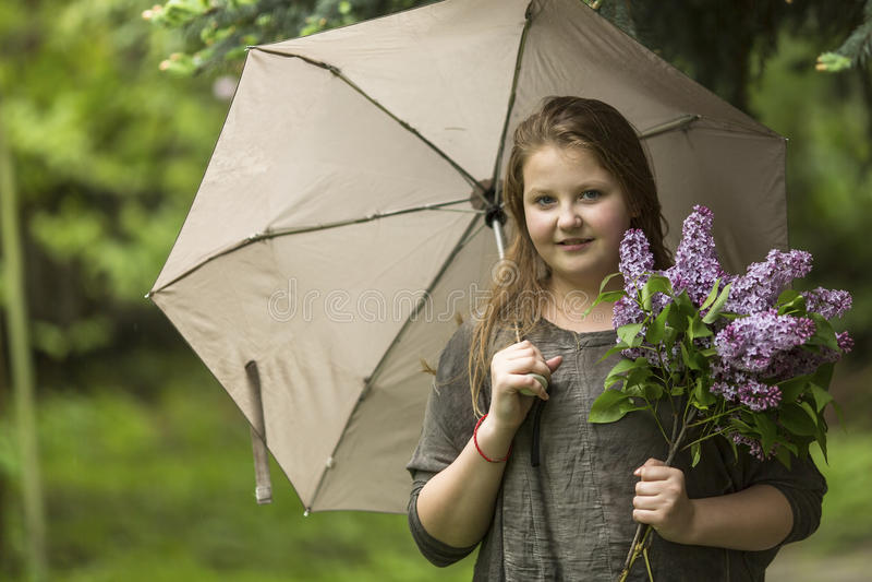 Fille de l'adolescence avec un parapluie et un bouquet des lilas image stock