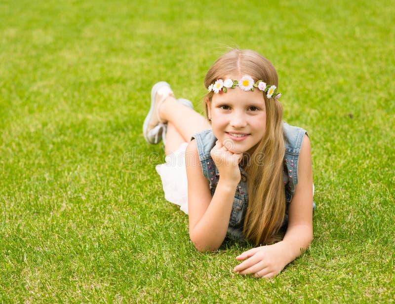 Fille de l'adolescence avec une guirlande des fleurs se trouvant sur une herbe verte fraîche photo stock
