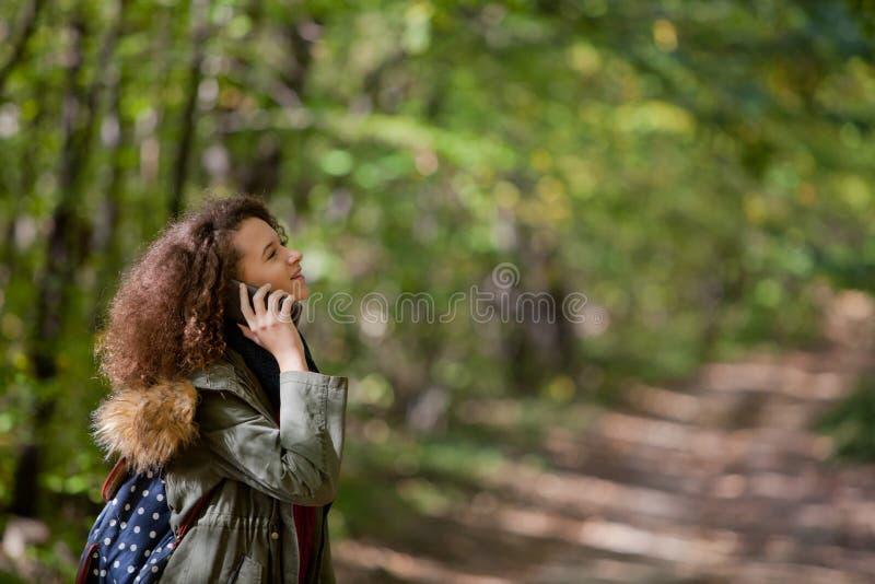 Fille de l'adolescence de cheveux bouclés avec le smartphone dans la forêt d'automne image libre de droits