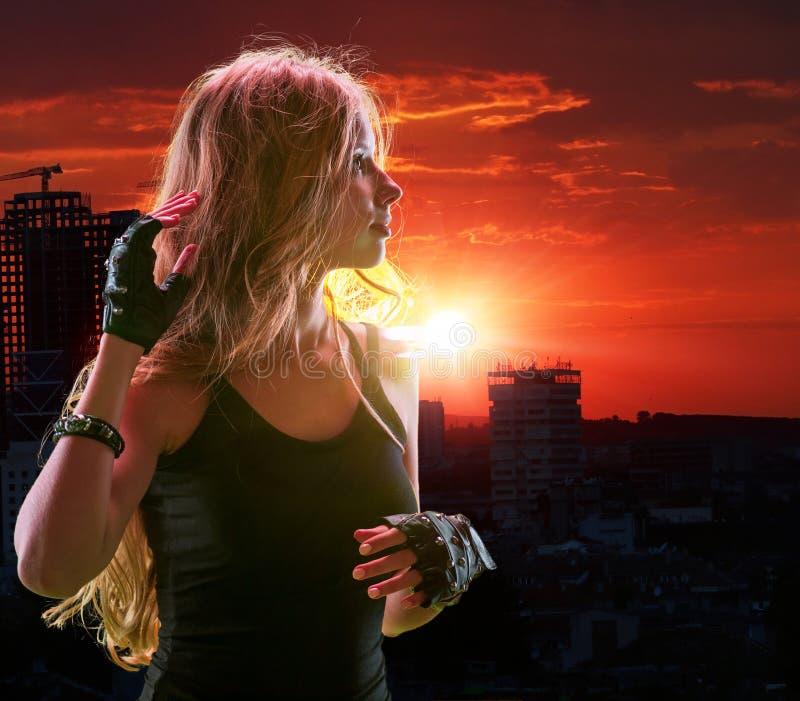 Fille de l'adolescence dans la ville regardant le coucher du soleil photographie stock